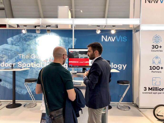 Solution Manager Georgios Pavlidis discussing Building Information Modeling with a booth visitor.